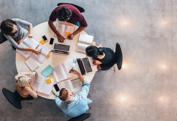 This photo shows a top view of group of students studying together at table.