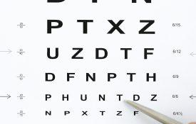 Ballpoint pen pointing to letter on eye exam chart.