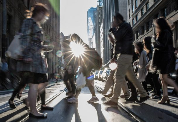 This is a photo of people crossing the street in a downtown area.
