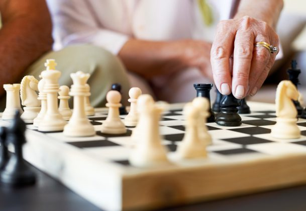 This is a cropped closeup of a senior couple enjoying a game of chess