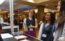 An APS Student Volunteer talks with attendees at the APS Registration Booth