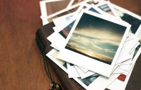 Old polaroid pictures of a sunset piled on top of a leather journal.