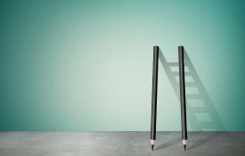Two pencils propped on wall with ladder shadow