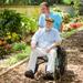 person_pushing_elderly_man_in_sunshine_thumbnail