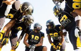 Football team huddled during time out while playing game
