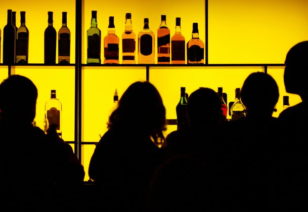 Silhouettes of people at a cocktail bar