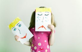 Little blonde girls holding happy and sad face masks symbolizing changing emotions