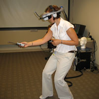 A lab member demonstrates virtual reality gear worn by study participants.