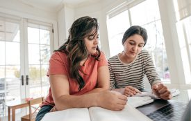 Mother reviewing school assignment with her daughter