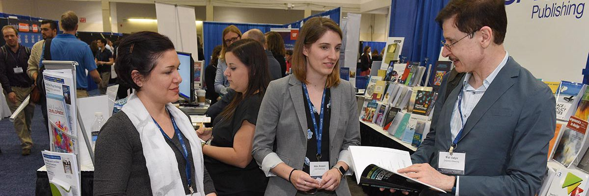APS Exhibitor chatting with attendees at exhibit booth.