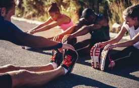 Multi-ethnic group of young adult athletes doing hamstring stretch exercises after a running workout