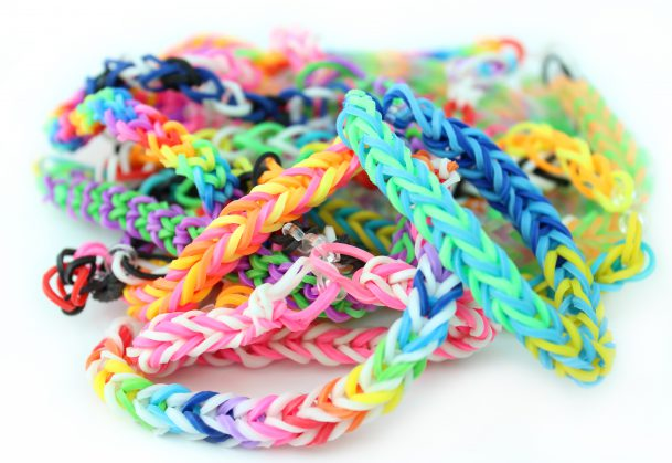 Photo showing a pile of rainbow coloured loom bracelets, made from coloured rubber loom bands. These friendship bracelets are popular with young children, who weave the rubber bands together using a simple plastic loom device.