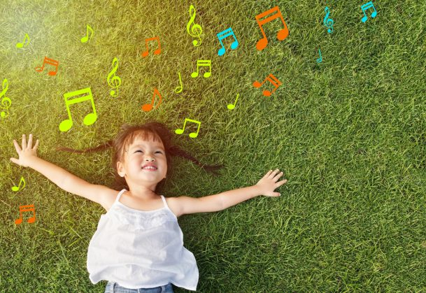 Little girl smiling and lying on grass with music notes around her