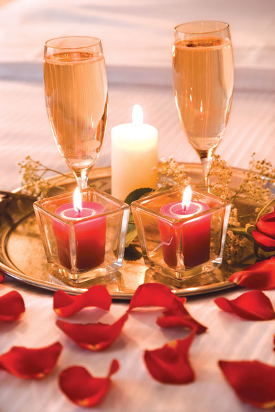 This is a photo of two glasses, candles, and rose petals in a romantic display..