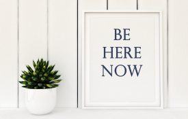 "This is a photo of a framed poster that says ""be here now"""