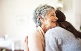 Shot of a senior woman hugging a young woman in a retirement home