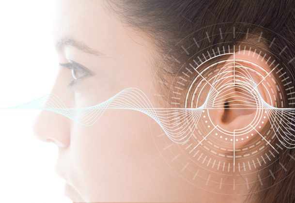 Hearing test showing ear of young woman with sound waves