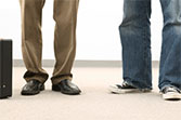 This is a photo of a man in dress pants and a man in jeans.