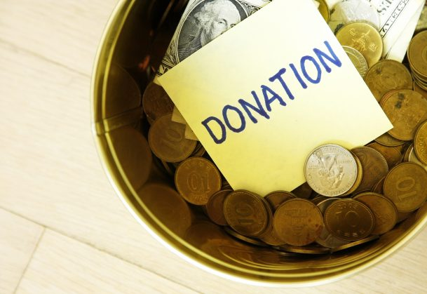 Donation in tin can with coins and one dollars