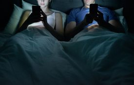 Cropped shot of a young couple using their cellphones in bed at night