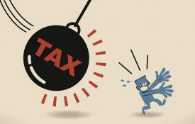 Businessman running away from huge pendulum with message tax