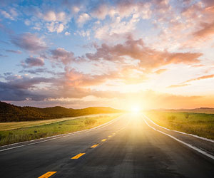 This is an image of a sunrise over a road in the countryside.