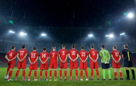 Rear view of football team standing in a row during national anthem before match.