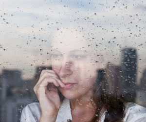 This is a photo of a woman looking out a rainy window.