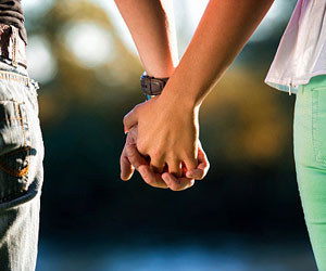 This is a photo of a couple holding hands.