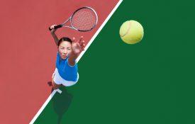 Young Asian woman serving tennis ball.