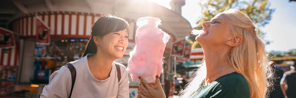 Photo of two young women sharing cotton candy at an amusement park