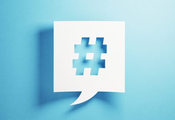 White chat bubble containing a hashtag, against a blue background.
