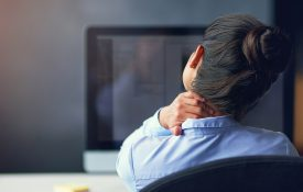 This is a photo of a woman in the office who is suffering from neck pain
