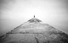 Man alone on the edge of a pier
