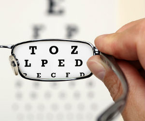 This is a photo of a person holding glasses in front of an eye chart.