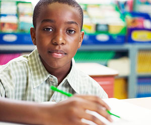 This is a photo of a black student sitting at a desk.