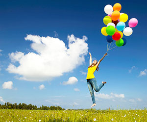This is a photo of a happy woman jumping, holding balloons.