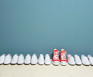 This is a photo of a pair of red shoes in a line of white shoes.