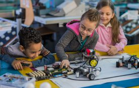 Group of small kids working on motherboard and robots in laboratory.
