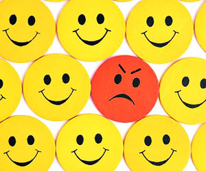 This is a photo of an angry face amidst smiley faces.