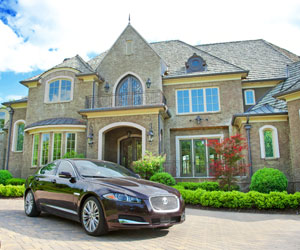 This is a photo of a mansion with an expensive car out front.