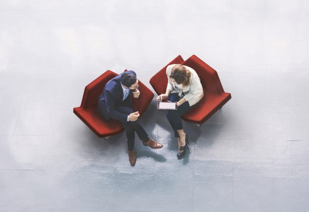 A high-angle view of a businessman and a businesswoman sitting in the office building lobby and using a tablet computer