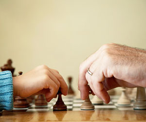 This is a photo of an adult and child playing a game of chess.