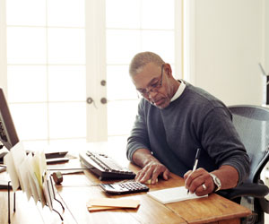 This is a photo of a man writing at a desk.