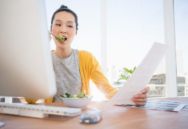 Businesswoman eating a salad while working