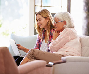 This is a photo of an older woman and a younger woman looking at a computer.