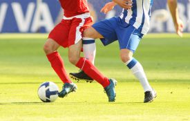 Two soccer players vying for the ball