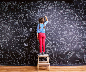 This is a photo of a girl doing math on a chalkboard.