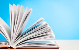 This is a photo of an open book on desk against a blue background