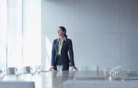 Businesswoman standing alone in conference room